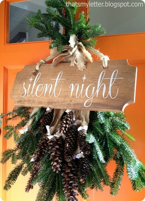 Christmas Decorating Ideas ~ Skip the traditional wreath this Christmas and layer evergreen and pine cones with a handmade sign inspired by Pottery Barn.