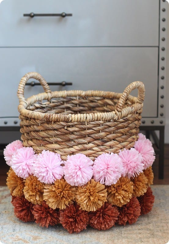 DIY Home Decor | Anthropologie Knock Off Pom Pom Basket ~ Learn how to make the perfect pom from raffia with this tutorial. They're adorable on a basket, wreath, garland...!
