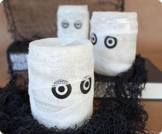 DIY Halloween Decorations ~ These Pottery Barn knock off mummy luminaries were made for only a couple of dollars using upcycled salsa jars!