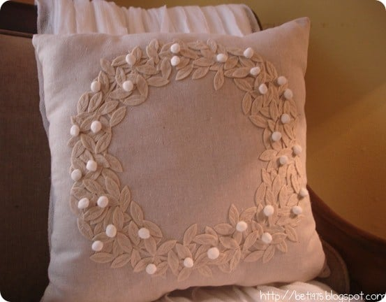 DIY Christmas Wreath Pillow ~ This pretty wreath pillow is just as pretty as Pottery Barn's and requireds just felt and pom poms.