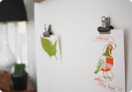DIY Wall Decor ~ Instead of frames, use vintage metal clips to display artwork on the wall.