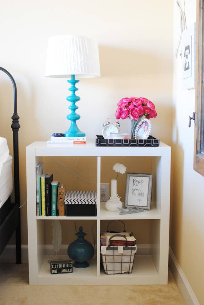 Lamps, books, a clock, flowers, and art make for a stylish and functional nightstand.