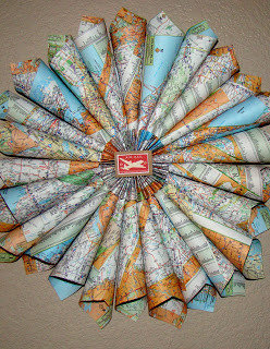 Recycle an worn out map into a door wreath.