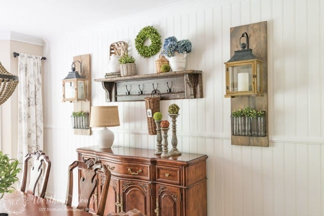 DIY-farmhouse-style-planked-shiplap-wall-with-a-vintage-mantel-shelf-buffet-and-Fixer-Upper-style-wall-lanterns