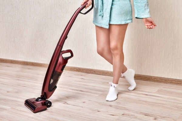 cordless stick vacuum held by woman