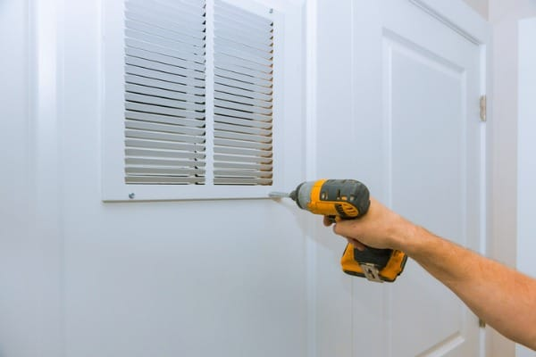man holding dril installing the wall vent