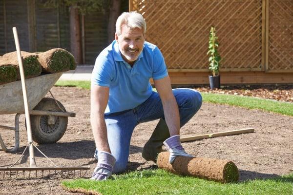 man laying turf on new lawn