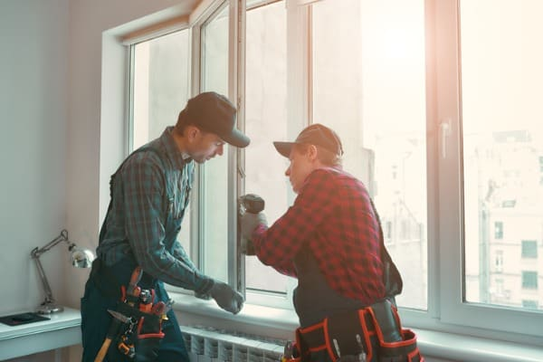 two men install replacement window