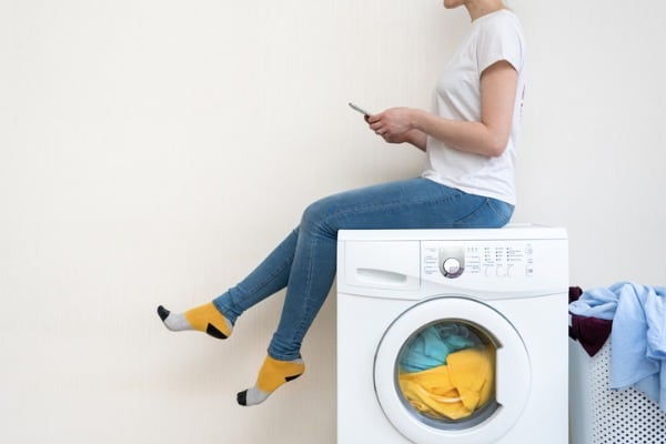 woman sit above washer