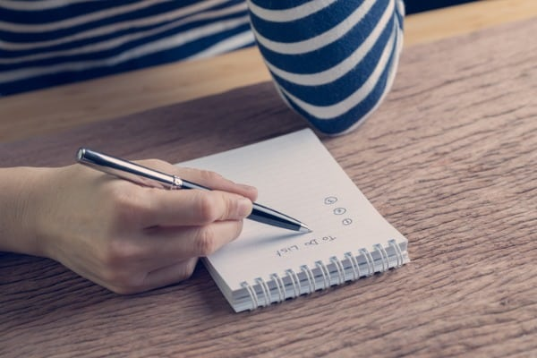 hand holding pen writing a list