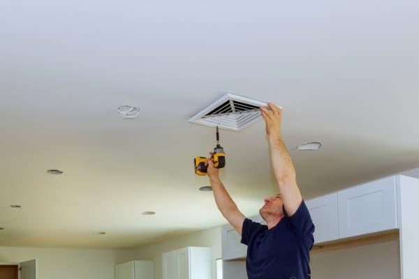 worker installing ventilation cover