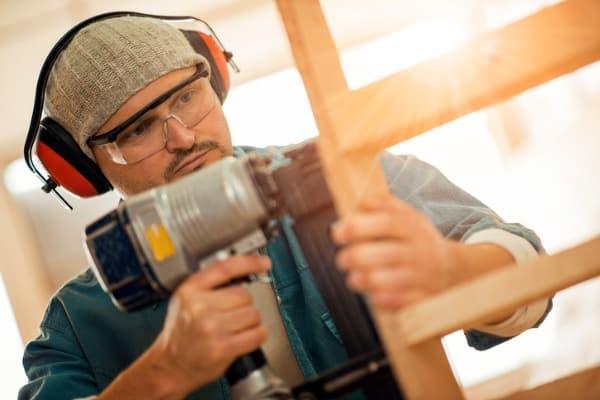young carpenter with nail gun
