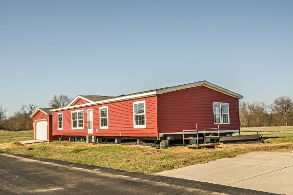 New manufactured home with red vinyl siding and windows with white lineals