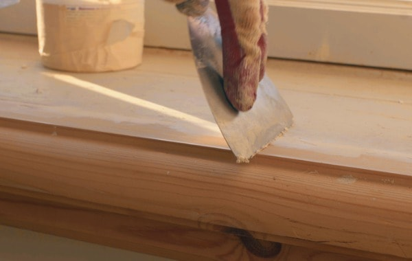 Scraping wood filler onto wood