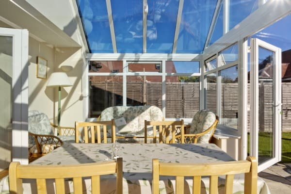 open air conservatory with tables and yellow chairs picture
