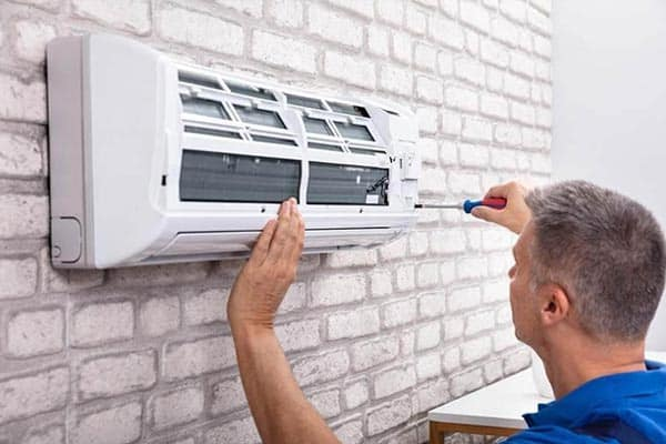 A/C repair tech working on unit