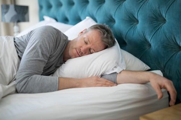 man-sleeping-on-bed-in-bedroom