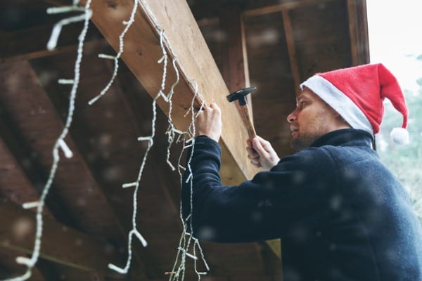 man with santa hat decorating the house
