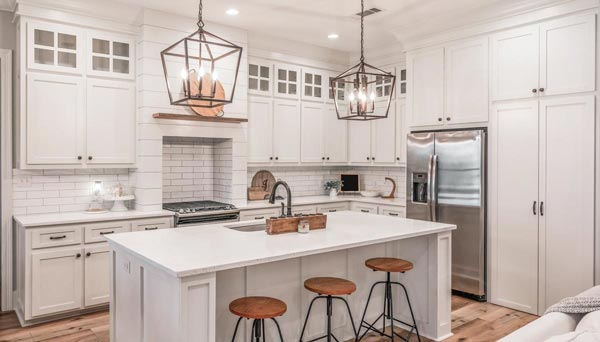 The pristine white kitchen is equipped with stainless steel appliances