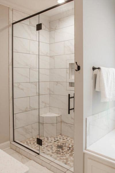 A walk-in shower with marble tiled walls, pebble flooring, inset shelves, and a corner built-in seat