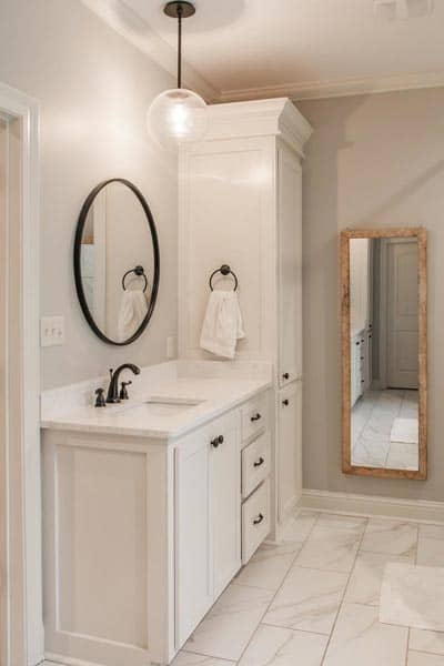A full-length wooden framed mirror that complements the white vanity fitted with wrought iron fixtures