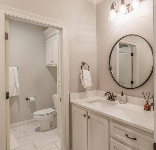 The bathroom carries a white aesthetic, a white vanity, and a toilet room with marble tiled flooring, they are further balanced with iron fixtures