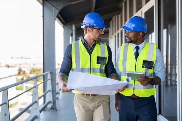 contractors-discussing-plan-at-construction-site