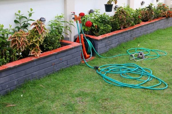 watering-hose-equipment-in-green-grass-of-backyard