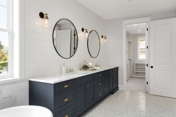 bathroom in new luxury home with two sinks and dark blue cabinets