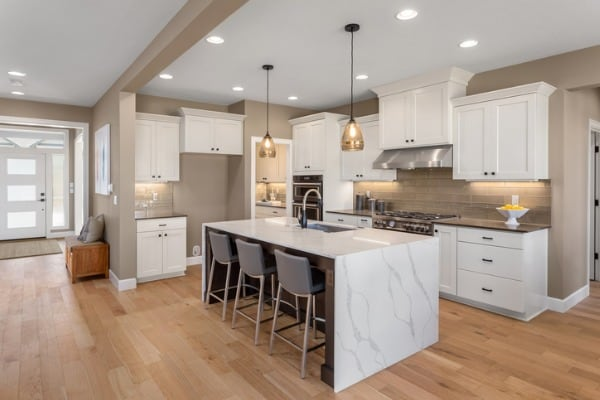 beautiful kitchen in new home with island pendant lights and hardwood 1