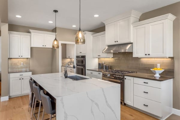 beautiful kitchen in new home with island pendant lights and hardwood