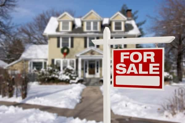 home-for-sale-sign-in-front-of-snowy