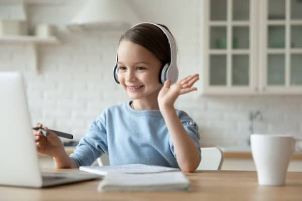 little girl have video call on laptop at home