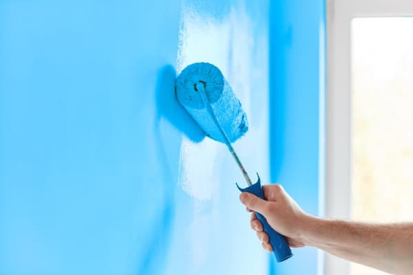 male-hand-painting-wall-with-paint-roller