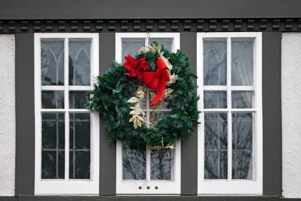 old fashioned wooden casement window decorated with christmas wreath