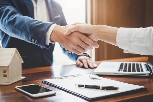 real estate agent and customers shaking hands together celebrating