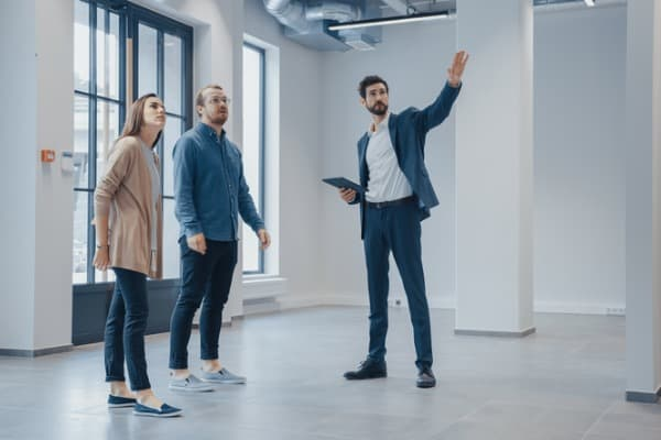 real estate agent showing a new empty office space to young male