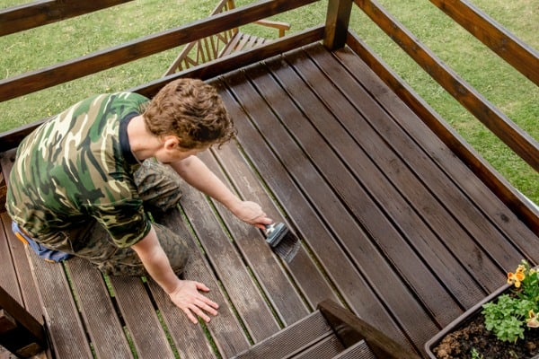 top-view-of-young-man-staining-garden-terrace-wooden-boards-outdoors