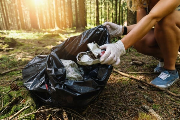 woman hand picking up a canned tin to clean up the forest