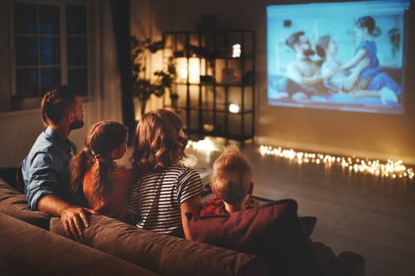 family mother father and children watching projector tv movies