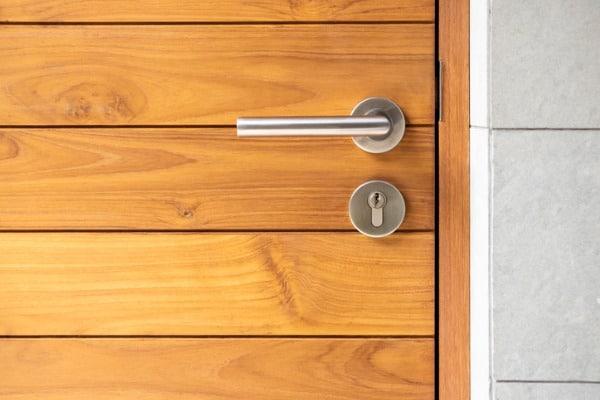 stainless steel door handle and wooden door