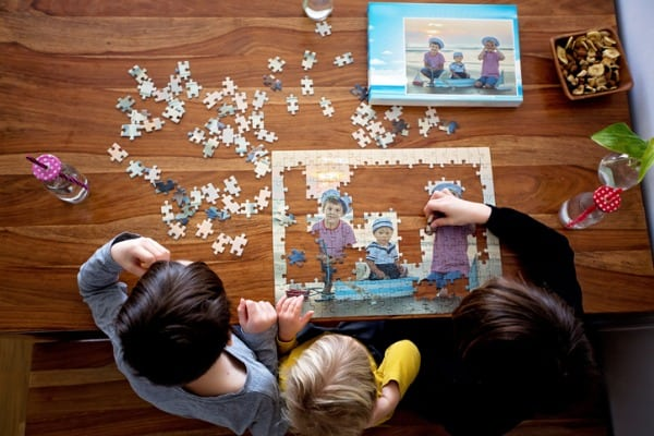 three children boys assembling puzzle with their picture